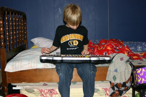 Sage composing a song on one of his keyboards.